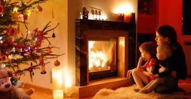 Baby proof fireplace: A family cuddling in front of a warm fire