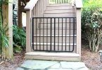 Outdoor baby gate: black gate at foot of stairs