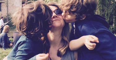 A mother of boys being kissed on the cheek by her sons