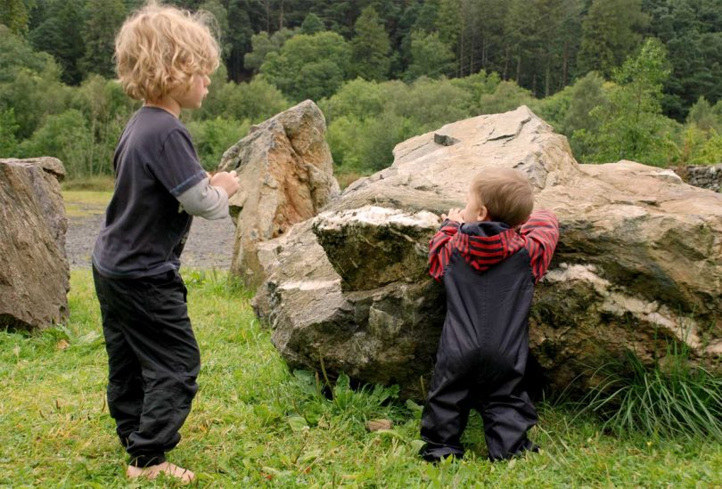 Camping with a baby: two young children playing in the countryside