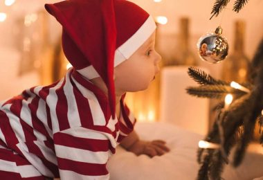 Crawling baby looking into Christmas bauble